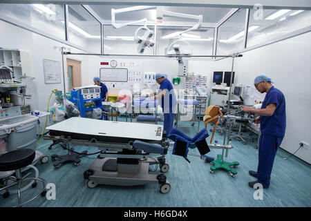 Hospital staff in an operating theatre preparing for an operation - Stock Photo