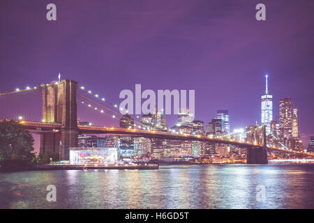 Beautiful night view of New York City skyline and Brooklyn Bridge in NYC - Stock Photo