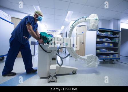A hospital technician pushes an X Ray machine along a corridor - Stock Photo