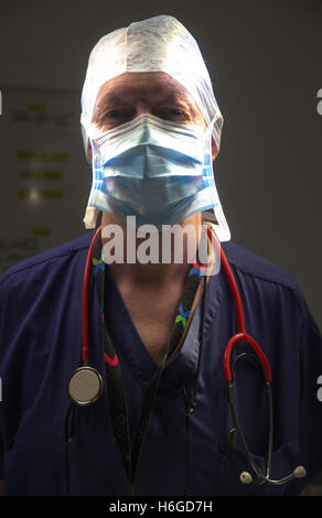 A hospital surgeon in a theatre just prior to an operation with moody lighting - Stock Photo