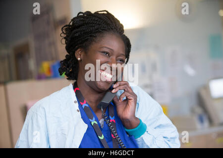 A happy nurse in a ward chatting about a patient on the phone