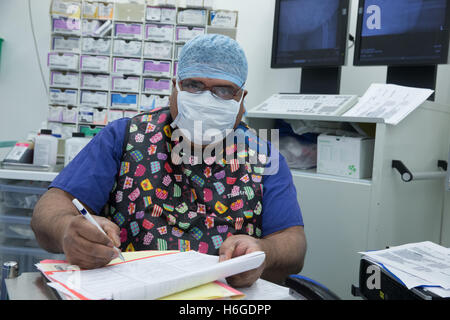A hospital nurse wearing scrubs and a surgical mask in an operating theatre makes notes during an operation - Stock Photo