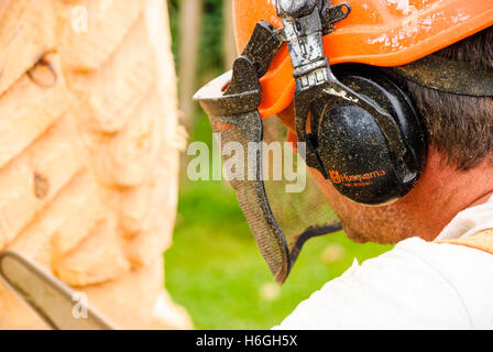 A man wears a Husqvarna safety helmet with ear defenders and face mask while he uses a chainsaw to carve a large - Stock Photo