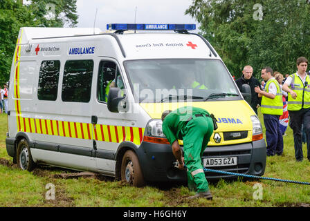 Paramedic attaches a tow rope to an ambulance stuck in mud at a festival - Stock Photo
