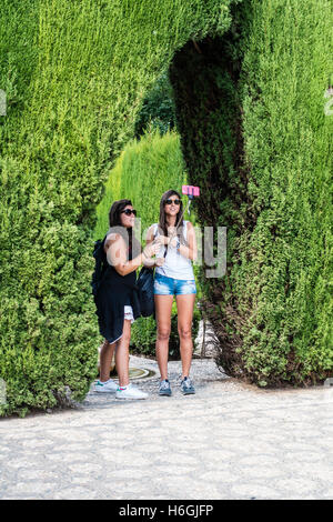 Two young female tourists taking selfie in the garden of the Alhambra, Granada, Spain. - Stock Photo