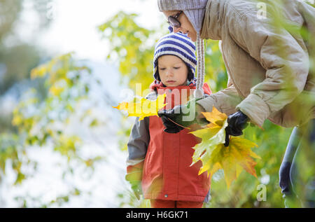Son and mother looking at maple leaf in autumn park - Stock Photo