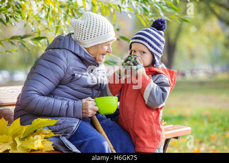 Senior woman and her great grandson drinking hot tea in autumn park - Stock Photo