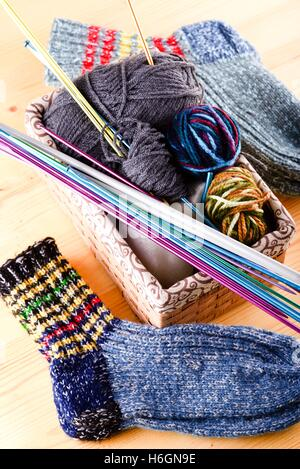 Vertical photo of box full of wool clues and several knitting needles and other accessories. Two pair of socks are - Stock Photo