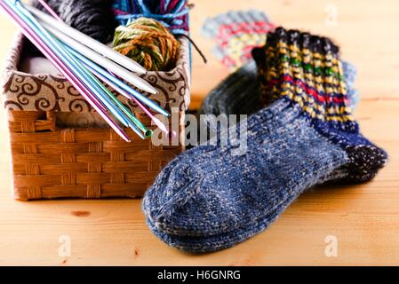 Horizontal photo of box full of wool clues and several knitting needles and other accessories. Two pair of socks - Stock Photo