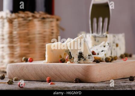 Horizontal photo of  blue cheese portion placed on wooden board with colour pepper seeds around. Bottle of wine - Stock Photo
