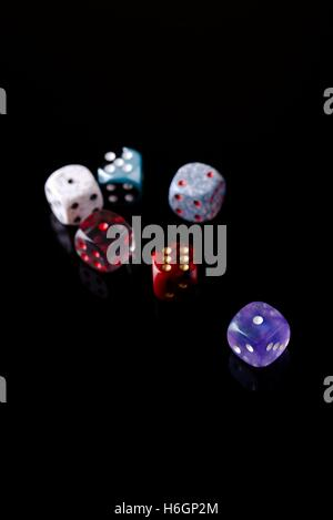 Vertical photo with several color dices which are placed on black board with nice reflections. Few dices are semi - Stock Photo