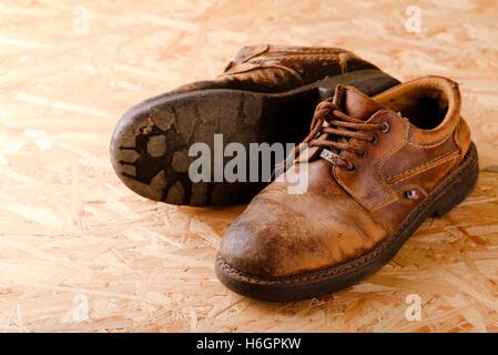 Horizontal photo of two old worn brown leather shoes with damaged laces. Pair of boots is placed on wooden OSB board. - Stock Photo