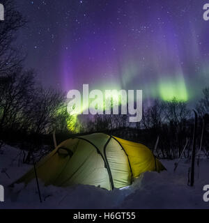 Tenting under the auroras in Finland - Stock Photo