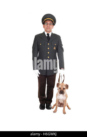 A security guard with his sharpei puppy dog standing in the studio in a dark olive green jacket and brown pants - Stock Photo