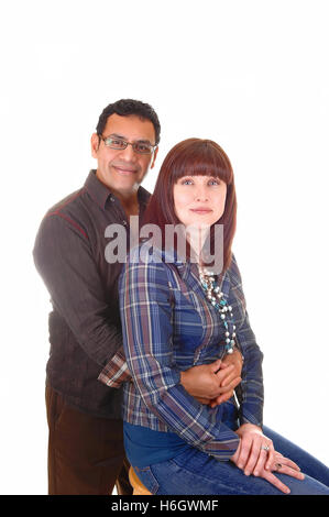 A nice couples in there forties, she sitting on a chair and he is hugging her from the back, for white background. - Stock Photo