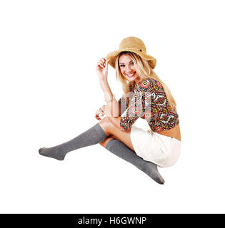 A lovely slim young girl crouching on the floor in a white skirt and colorful  top in gray socks and beige straw - Stock Photo