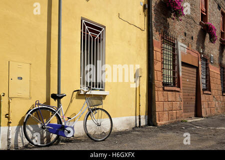 woman's bicycle propped against a yellow wall in Ferrara, Italy. - Stock Photo