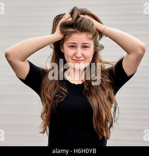 Young woman with long hair grabbing hair with a worried expression - Stock Photo