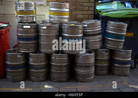 beer kegs stacked in alley for collection - Stock Photo