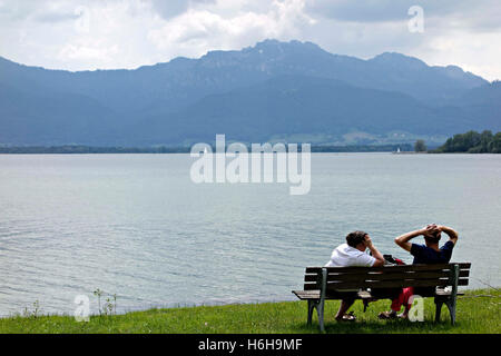 People on a park bench with view to the Kampenwand Mountain from the Fraueninsel, Chiemsee Chiemgau, Upper Bavaria - Stock Photo
