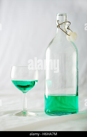 A glass and bottle of absinthe set on a white background - Stock Photo