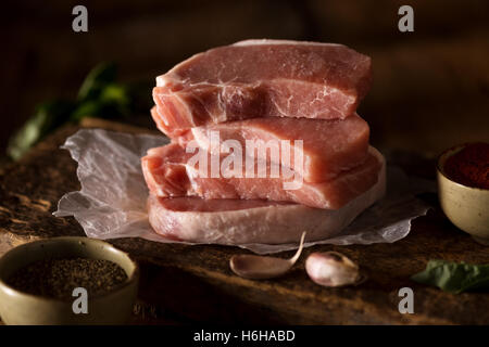 Raw pork chops ready to cook. Shot in subdued lighting - Stock Photo