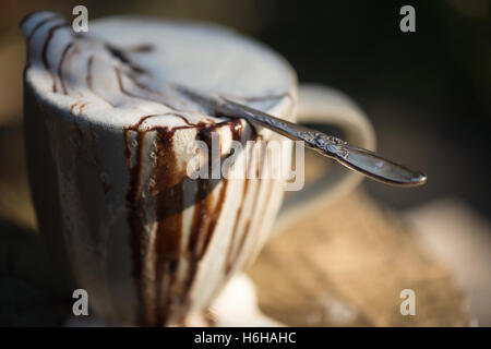 Very messy hot chocolate with whipped cream and chocolate sauce overflowing a mug set on tree stump - Stock Photo
