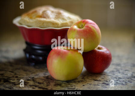 Apples with a apple pie on a kitchen counter. - Stock Photo