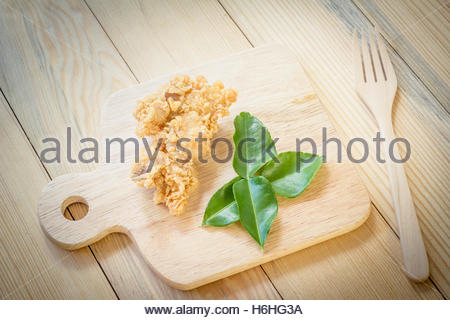 fried chicken in batter  on a wooden background. - Stock Photo