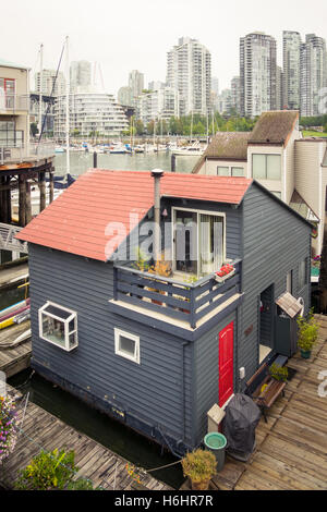 The Sea Village houseboats on Granville Island in Vancouver, Canada. The glass towers of Yaletown rise in the distance. - Stock Photo