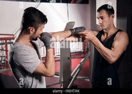 Trainer teaching a man how to box - Stock Photo