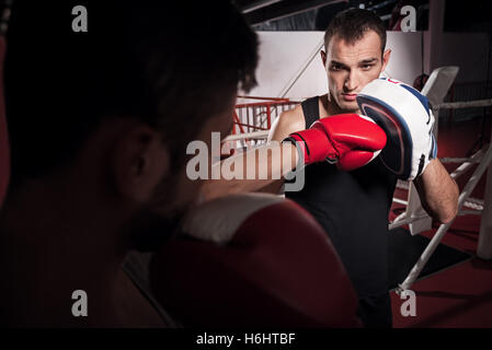 Young trainer holding boxing pad - Stock Photo
