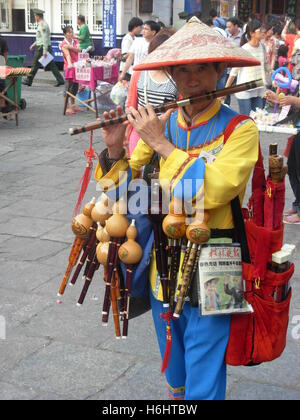 Chinese man playing and selling flute on the streets of Yangshuo, Guangxi province, China - Stock Photo