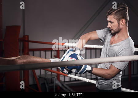 Close up of trainer with boxing pad - Stock Photo