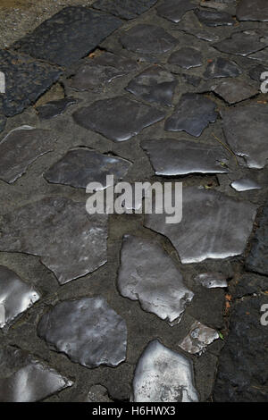 Stone set footpath footway polished with use over many years trafficked to a high shine buffed glossed glossy reflective - Stock Photo