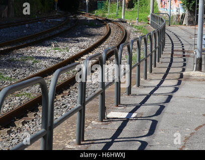 rail lines hoops barriers shadows linked rusty platform safety passengers cables poles electricity edge of platform - Stock Photo