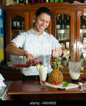 Big Corn Island, Nicaragua-April 2: Bartender mixing fresh pineapple pina colada at bar in hotel in Big Corn Island, - Stock Photo
