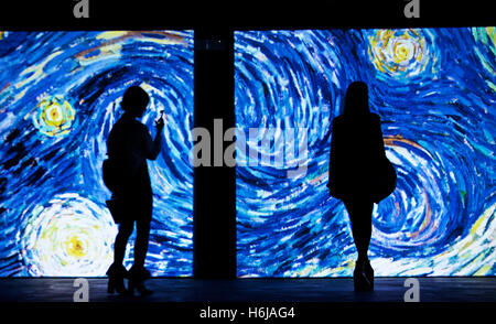Beijing, Oct. 25. 26th Mar, 2017. Two women view the image of the painting 'The Starry Night' at the 'Van Gogh Alive' - Stock Photo