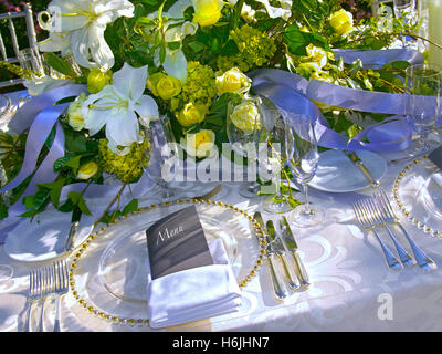 Luxurious table place setting in a sunny garden room lunch reception - Stock Photo