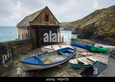 Fishing boats in front of the historic Old Royal National Lifeboat Institution station boathouse at Lizard Point, - Stock Photo