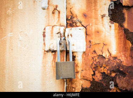 Close up of rusty metal door painted cream with a master padlock on it - Stock Photo