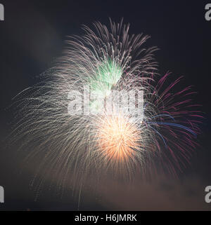 Exploding fireworks in green, orange, red and blue in a smokey night sky - Stock Photo