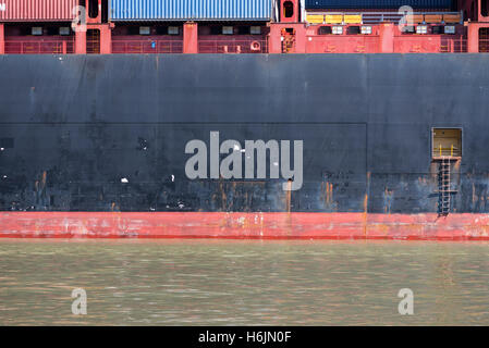 Open Door on Side of Container Ship as it floats down a river - Stock Photo