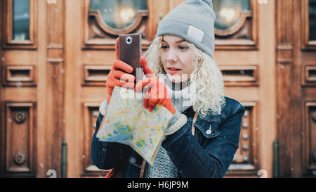 Young blond curly female tourist in warm clothes, red gloves and map photographs or taking a selfie on smartphone, - Stock Photo