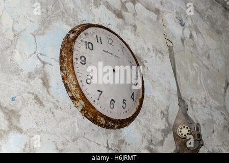The old clock hanging in abandoned building of Chernobyl - Stock Photo