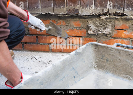 Home repair. Construction worker holding a trowel putty knife - Stock Photo