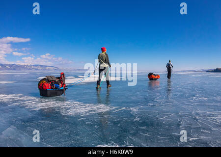 a woman and a man with a sledge and trekking pole is on the blue ice of Baikal - Stock Photo