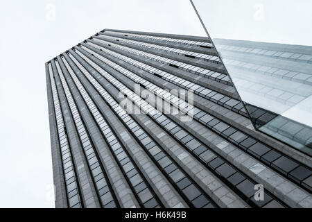 Modern office block seen in New York City. To the right is the glass cube entrance for the large Apple Store. - Stock Photo