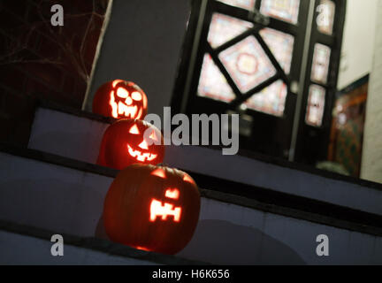 Halloween carved pumpkins placed on the doorstep of a house in north London, ahead of Halloween celebrations tomorrow. - Stock Photo