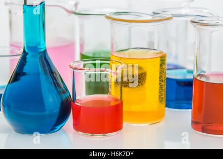 various beakers with different types of indicators in acids and basis, four colors of indicators in several solusions - Stock Photo